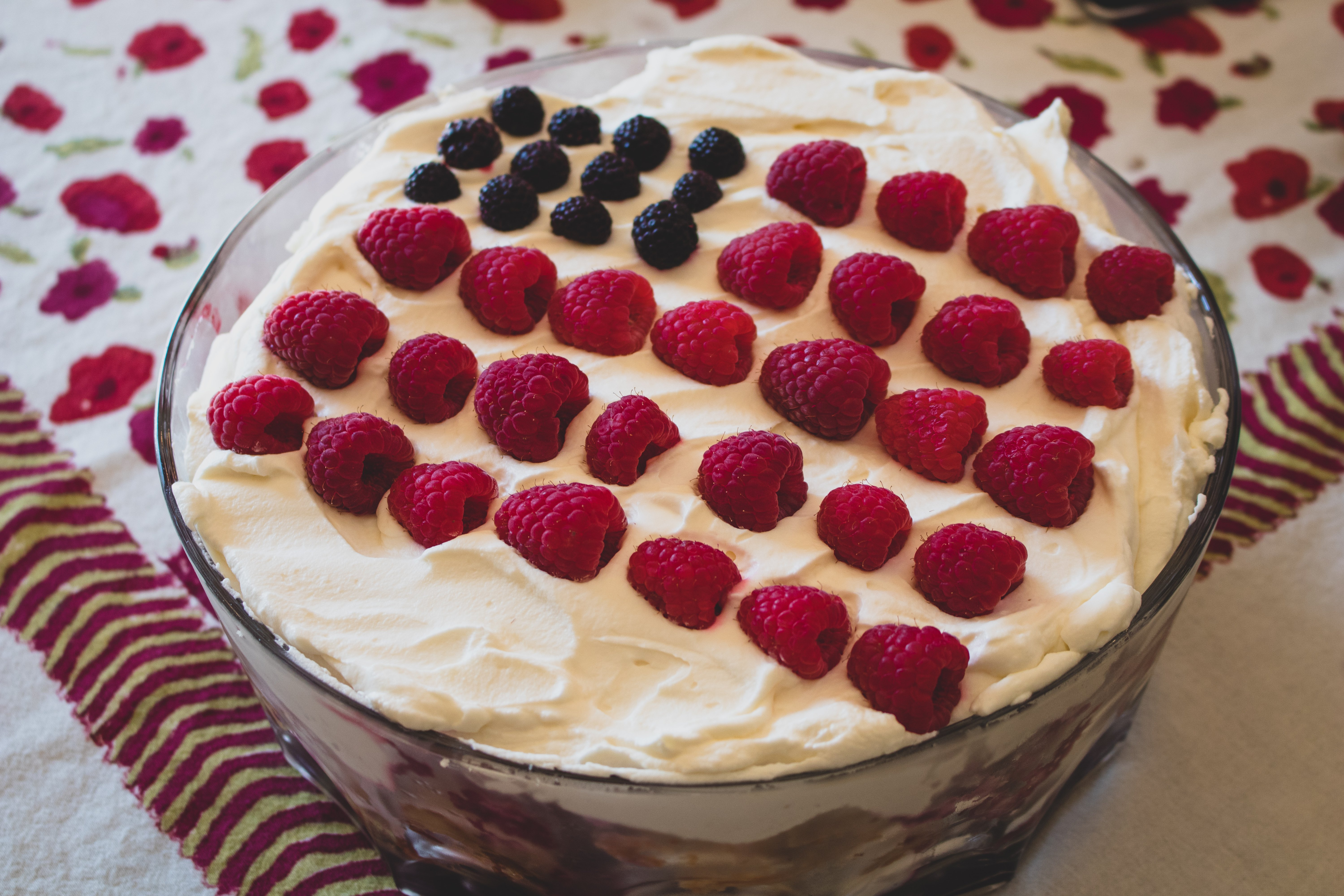 a trifle on a table topped with red raspberries and black raspberries arranged to resemble an American flag