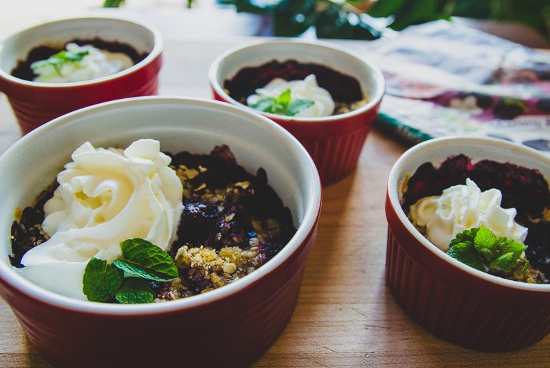 four servings of black raspberry cobbler topped with whipped cream and mint