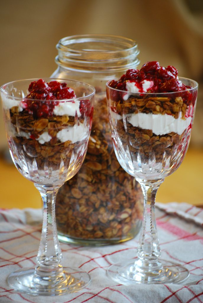 granola topped with alternating layers of yogurt and raspberry sauce