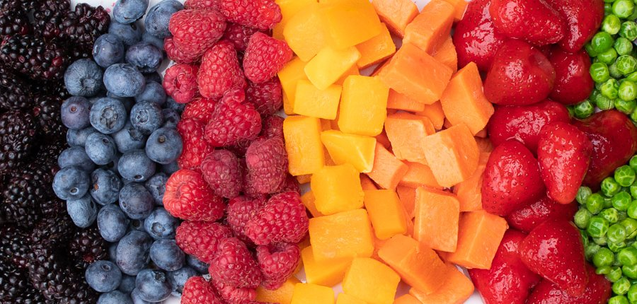 plate of marion blackberries, blueberries, diced butternut squash, diced sweet potato, strawberries and green pas arranged by color